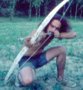 Tom testing a bow and arrow using a n arrowhead found in the fields.